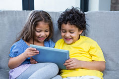 Cute siblings using tablet on the sofa Stock Image