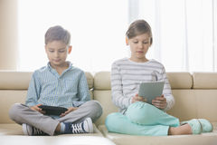 Cute siblings using technologies on sofa at home Stock Photo