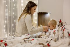 Cute sick child, boy, staying in bed, mom giving him medicine. And checking for fever stock photo