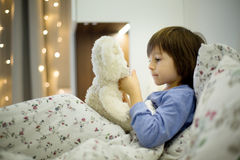 Cute sick child, boy, staying in bed, playing with teddy bear. Giving him medicine and checking for fever stock photo