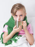 Sick girl with cup of tea Stock Image