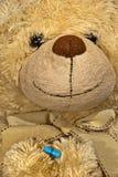 Cute sick teddy bear with a solution. Cute teddy bear with a blue vitamin Stock Image