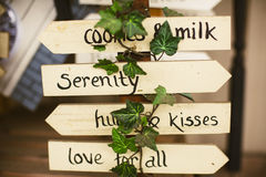 Cute sign with positive words on arrows. Handcrafted wooden signs with green plant stock photos