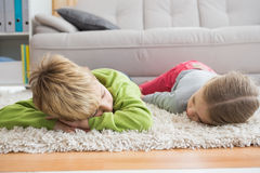 Cute silblings lying on the rug Stock Images