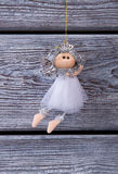 Cute silver fairy hanging on a wooden background. Royalty Free Stock Photos