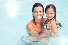 Single mother with young daughter smiling in pool stock photos