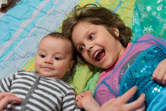 Cute sister with her little brother on a bed Stock Image