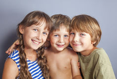 Cute sister hugging younger brothers Royalty Free Stock Image