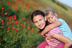 Cute sisters. Two young sisters hugging in the field of poppies Royalty Free Stock Photos