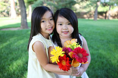 Cute Sisters with Flowers Royalty Free Stock Photos