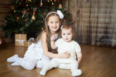 Cute sisters in front of decorated Christmas tree Royalty Free Stock Photography