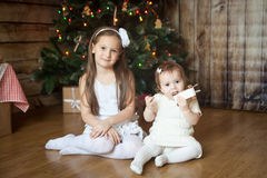 Cute sisters in front of decorated Christmas tree Royalty Free Stock Images