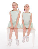 Cute sisters having fun sitting on a chair. Royalty Free Stock Photo