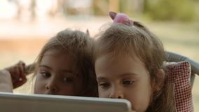 Cute sisters hold a tablet and watch a cartoon on it. Two small cute sisters hold a tablet and watch a cartoon on it stock footage