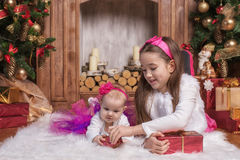 Cute sisters lying on white carpet near christmas trees, wearing pink skirts and red headbands. Smiling toddlers. Christmas gifts. Cute sisters lying on white Royalty Free Stock Images