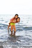 Cute sisters play inside the ocean