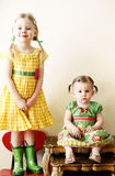 Cute Sisters portrait. An elder sister standing on a chair beside her cute little sister sitting on a table Stock Image