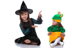 Cute sisters posing in costumes of witch and frog Stock Photography