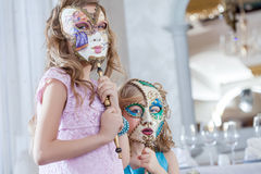 Cute sisters posing hiding faces behind masks Stock Photography