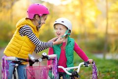 Cute sisters riding bikes in a city park on sunny autumn day. Active family leisure with kids. Children wearing safety hemet while. Cute little sisters riding royalty free stock photography