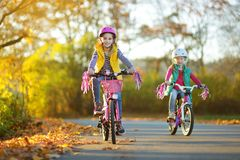 Cute sisters riding bikes in a city park on sunny autumn day. Active family leisure with kids. Children wearing safety hemet while. Cute little sisters riding royalty free stock image