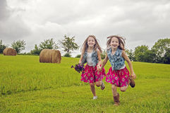 Cute sisters running in a pasture Royalty Free Stock Photo
