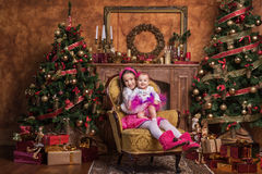 Cute sisters sitting near christmas trees. Cute sisters sitting on armchair near christmas trees, wearing pink skirts and red headbands. Smiling toddlers Stock Photo