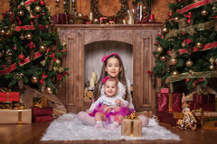 Cute sisters sitting near christmas trees. Cute sisters sitting on white carpet near christmas trees, wearing pink skirts and red headbands. Smiling toddlers Royalty Free Stock Image