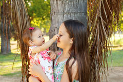 Cute sisters teen and baby girl playing in park Stock Photo