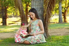 Cute sisters teen and baby girl reading book. On green grass near palm tree in park. Selective focus Royalty Free Stock Image