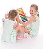 Cute sisters work in the Montessori environment. Stock Photos