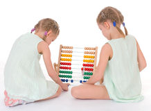 Cute sisters work in the Montessori environment. Royalty Free Stock Image