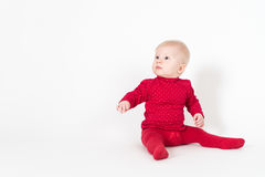 Cute sitting baby in red on white background stock images