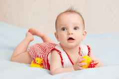 Cute six month old baby lying with toy duck Stock Images