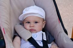 Cute six months old baby bou in the pushchair wih mosquito bites on his face.  stock images
