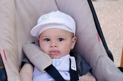 Cute six months old baby bou in the pushchair wih mosquito bites on his face.  stock image