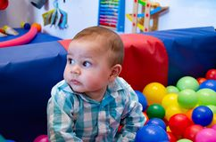 Cute six months old baby boy playing with colorful balls in the childcare.  royalty free stock photo