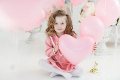 Cute six year old girl in pink dress with pink balloons in the shape of heart. A little girl of 6 years with long curly hair, dressed in a pink dress and white Royalty Free Stock Photos