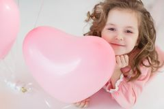 Cute six year old girl in pink dress with pink balloons in the shape of heart Royalty Free Stock Images