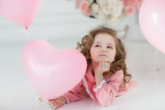 Cute six year old girl in pink dress with pink balloons in the shape of heart. A little girl of 6 years with long curly hair, dressed in a pink dress and white Stock Image