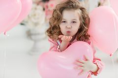 Cute six year old girl in pink dress with pink balloons in the shape of heart. A little girl of 6 years with long curly hair, dressed in a pink dress and white Stock Photography