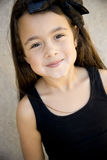 Cute six year old girl. Very cute six year old brunette girl looking up at camera, shy little smile, ribbon in hair Royalty Free Stock Photo