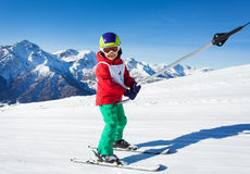 Cute skier at surface lift against mountain scene Royalty Free Stock Photo