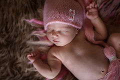 Cute sleeper newborn baby girl in pink cap on wool Royalty Free Stock Photos
