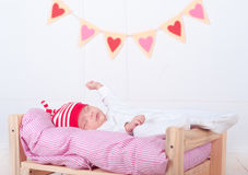 Cute sleeping baby. Cute baby boy sleeping on soft bed with valentines hearts on background Royalty Free Stock Photography