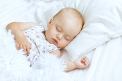 Cute Sleeping baby girl. Portrait of a cute sleeping baby girl in bed Royalty Free Stock Photos