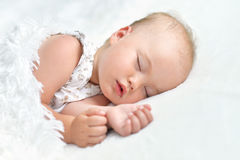 Cute Sleeping baby girl. Portrait of a cute sleeping baby girl in a bed Stock Images