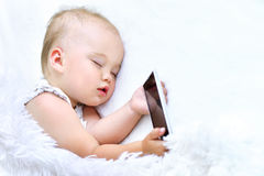 Cute Sleeping baby girl. With smartphone in bed Stock Image