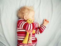 Cute sleeping blond baby with toy Royalty Free Stock Photo