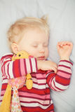 Cute sleeping blond baby with toy Stock Images